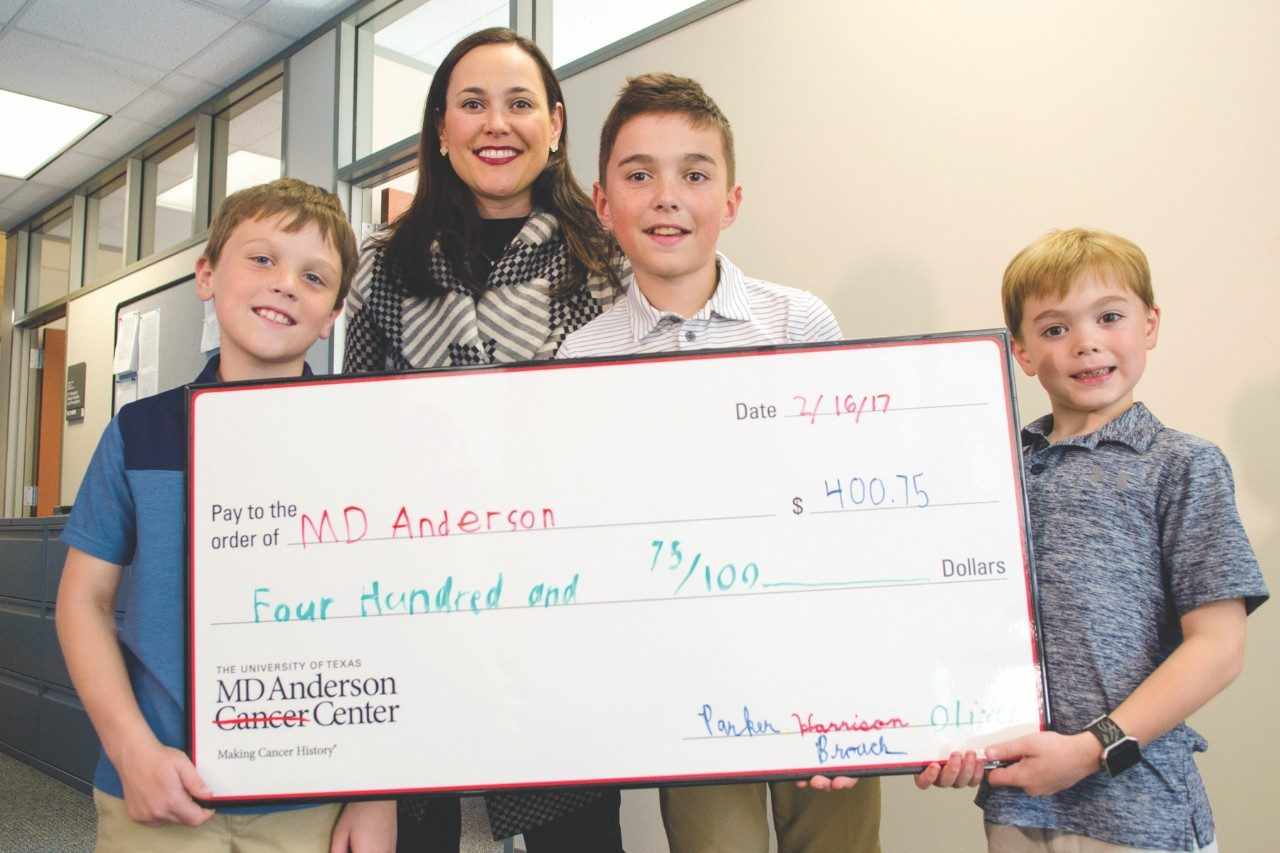 Parker, Harrison and Oliver Broach present MD Anderson Cancer Center with a $400 check for brain cancer research to honor their father's memory.