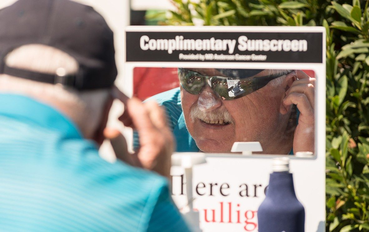 A spectator applies sunscreen at one of several kiosks, complete with mirrors to ensure proper coverage. Photo by Adolfo Chavez III