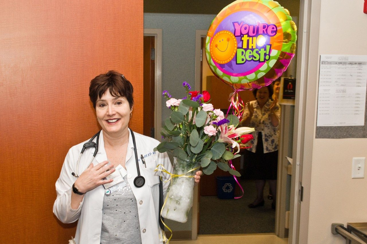 Peg Fields is all smiles as colleagues at MD Anderson's Mays Clinic surprise her with the news that she is the 2010 recipient of the Ethel Fleming Arceneaux Oustanding Nurse-Oncologist Award. Photo by Barry Smith.