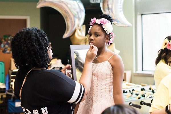 Volunteers make sure promgoers are hair- and makeup-ready.