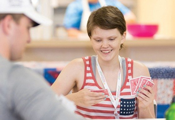Katsie Brock beats the summer heat with a game of cards at Camp A.O.K.