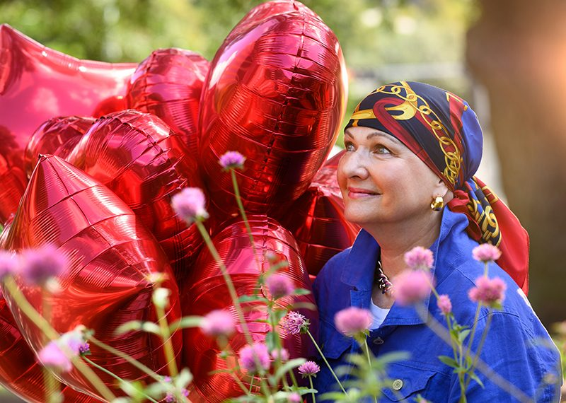 Woman in headscarf holds bouquet of red balloons