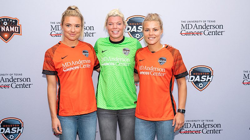 Kristie Mewis, Jane Campbell and Rachel Daly wear orange and green MD Anderson-branded Houston Dash jerseys