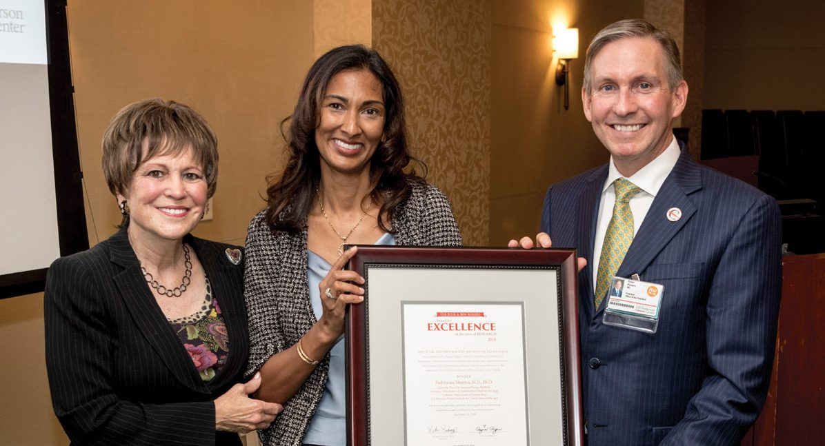 Padmanee Sharma, M.D., Ph.D. holds a framed certificate noting her $15,000 award as she poses with Regina Rogers and Peter WT Pisters, M.D.