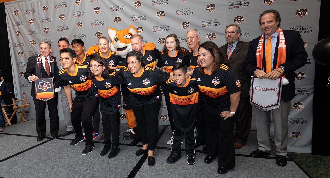 Cancer survivors wearing the Houston Dynamo's 2019 away jersey pose in a Starting XI-style formation.