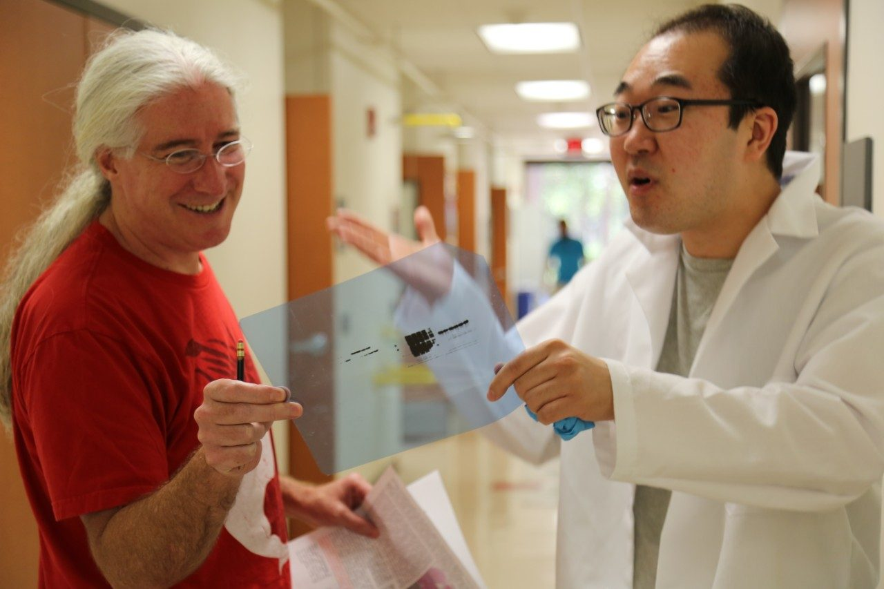 Mark Bedford and Dr. Narkhyun Bae discussing experimental results.