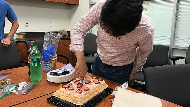 Jian Hu cutting birthday cake