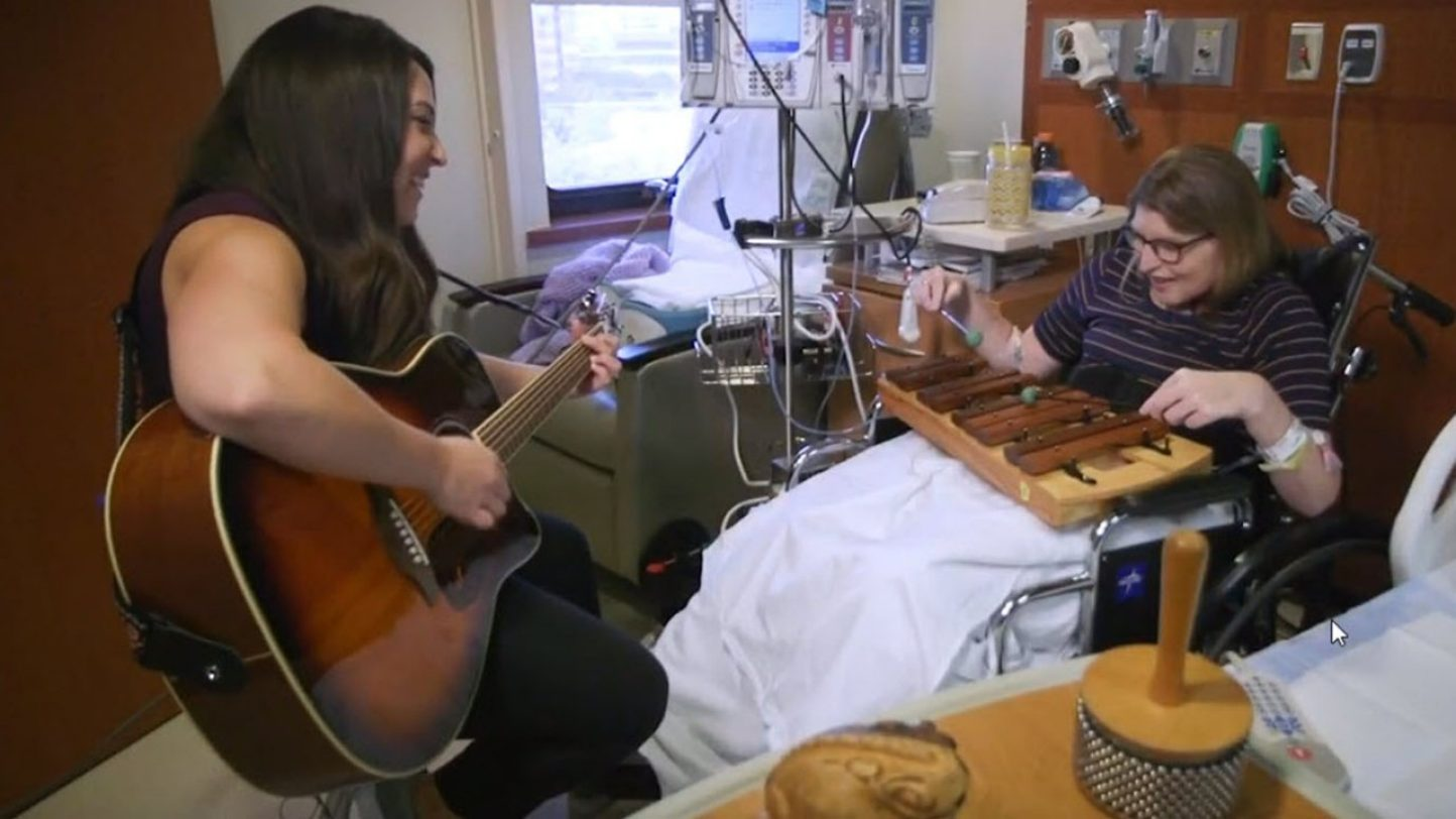 Sarah Folsom and patient playing music in patient's room